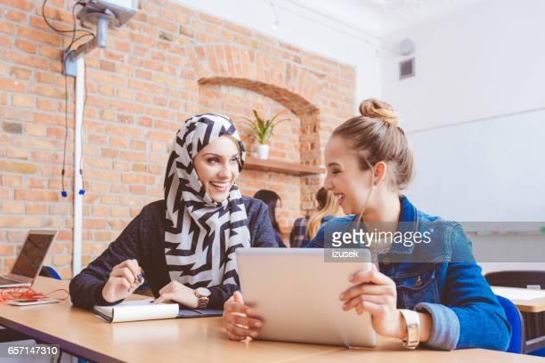 Multi ethnic female students during break in classroom