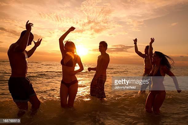 Multi étnica amigos bailando en la playa