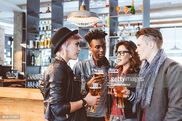 Multi ethnic friends drinking  beer in a pub