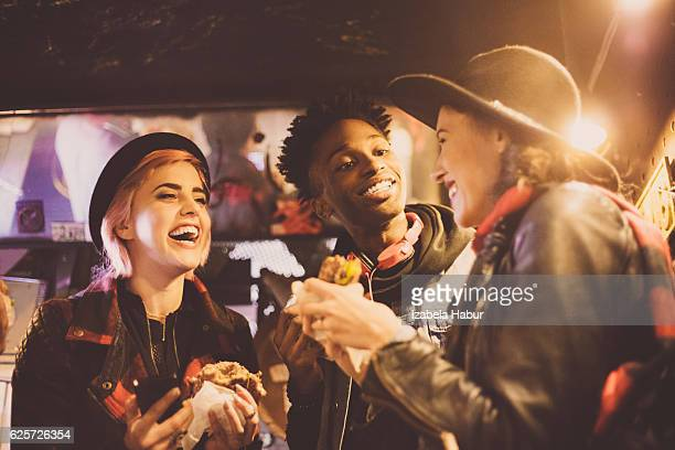 multi ethnic friends eating burgers in pub - street food stock pictures, royalty-free photos & images