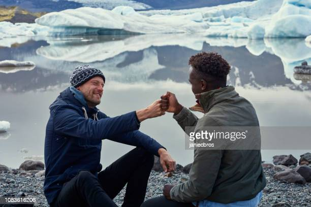 multi ethnic friends having fun at glacier lagoon - masculinity stock pictures, royalty-free photos & images