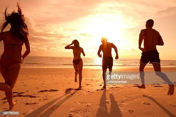 Multi ethnic friends running on the beach