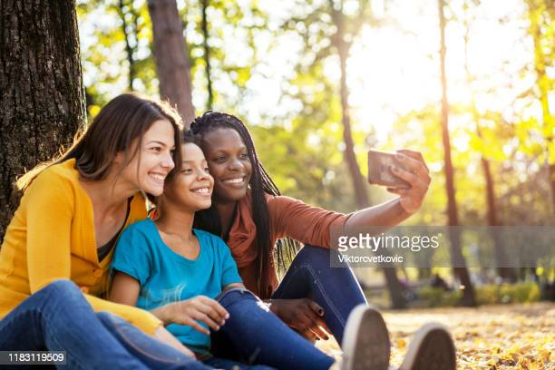 multi ethnic friends with child taking selfie - lgbtq  and female domestic life stock pictures, royalty-free photos & images