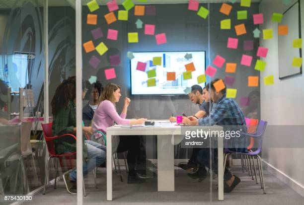 Multi ethnic group at a board meeting brainstorming ideas with adhevisve notes on the window glass