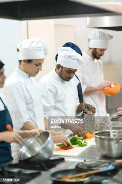 Multi ethnic group cooking meals at a kitchen's restaurant