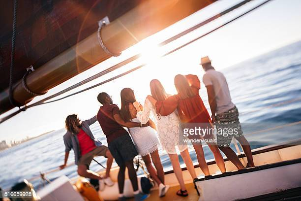 Multi ethnic group  friends looking at horizon from a yacht
