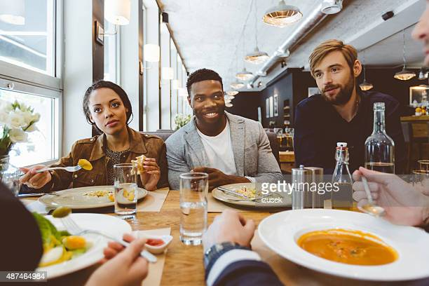 Multi ethnique groupe d'amis se restaurer et dîner dans un restaurant