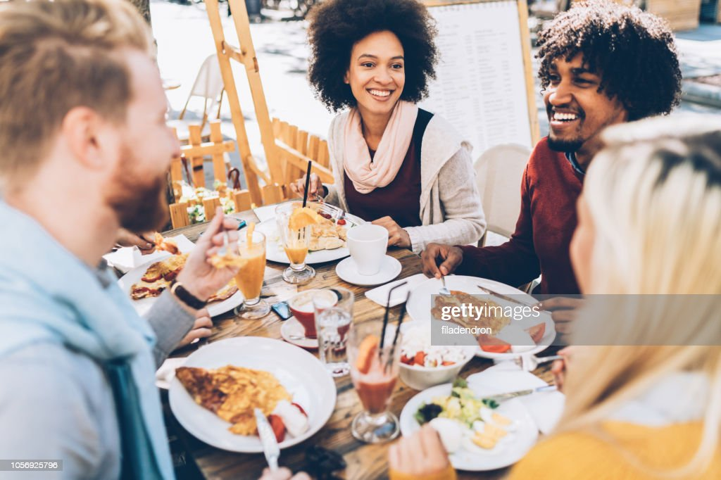 Multi ethnic group of friends eating lunch in a restaurant : Stock Photo
