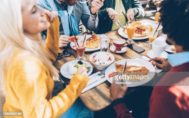 multi ethnic group of friends eating lunch in a restaurant - the brunch stock pictures, royalty-free photos & images