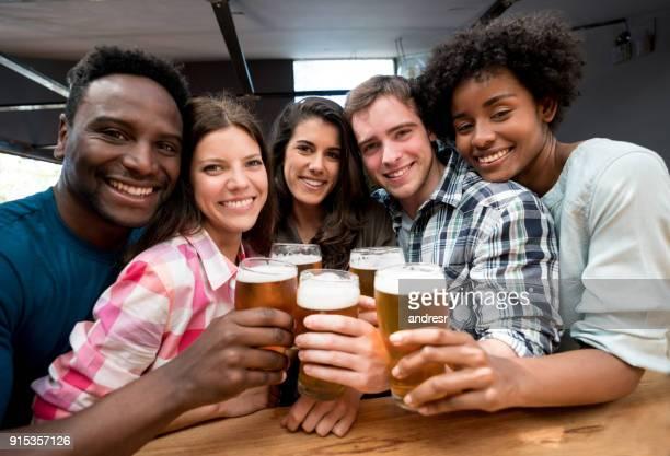 Multi ethnique groupe d'amis faire un toast et en regardant la caméra en souriant