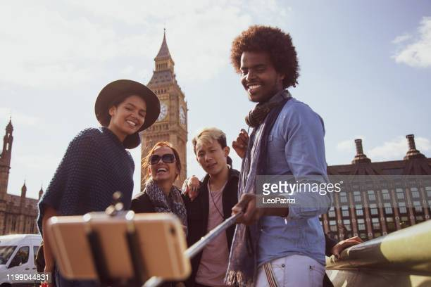 multi ethnic group of friends taking a selfie with bigben in central london - central london stock pictures, royalty-free photos & images