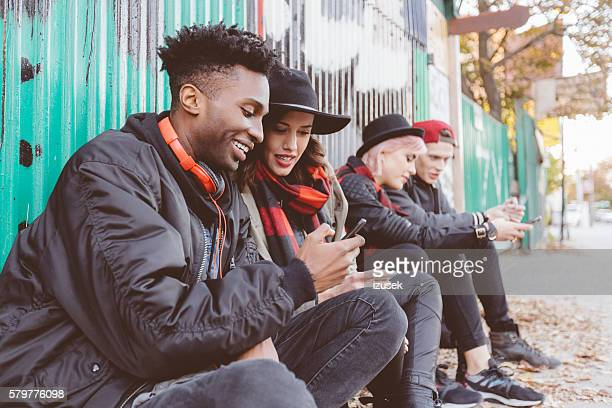 Multi ethnic group of hipsters outdoors usping phones