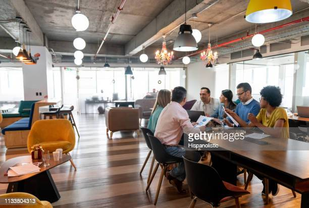 multi ethnic group of professionals at a coworking office in a meeting discussing something - business casual stock pictures, royalty-free photos & images