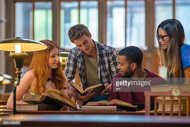multi ethnic group of students studying in a public library - literature stock pictures, royalty-free photos & images