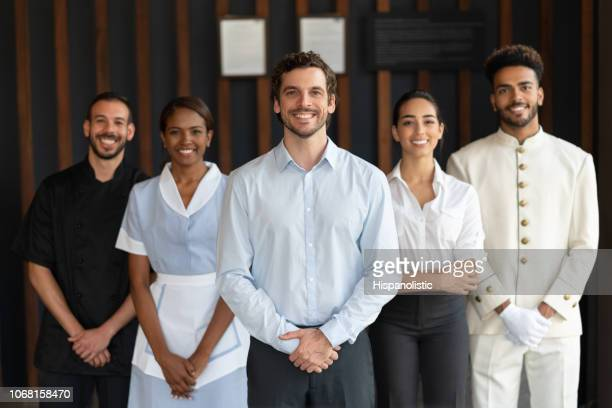 multi ethnic group of workers at a luxury hotel all looking at camera smiling - lavoratori dipendenti foto e immagini stock