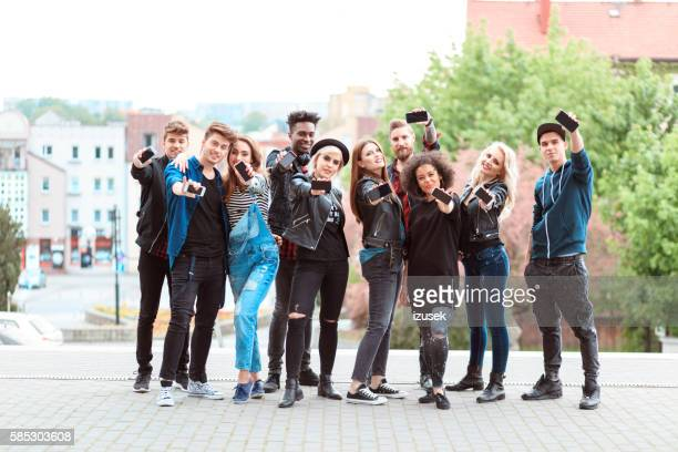 multi ethnic group of young people with mobile phones - izusek stock photos and pictures