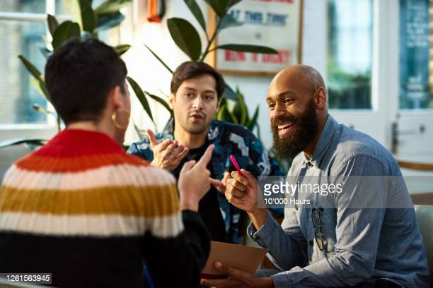 multi ethnic group sharing ideas in office - business stock pictures, royalty-free photos & images