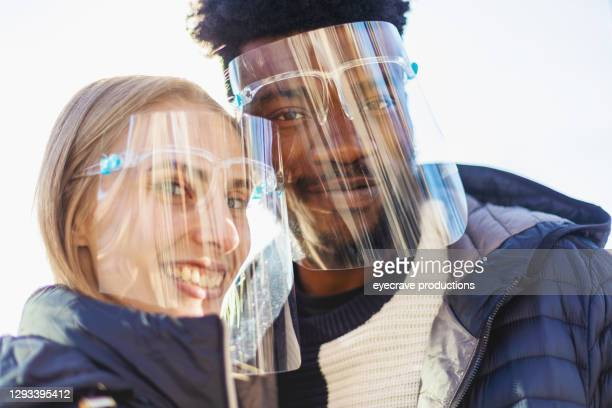 multi ethnic heterosexual couple wearing protective face shields photo series - eyecrave  stock pictures, royalty-free photos & images