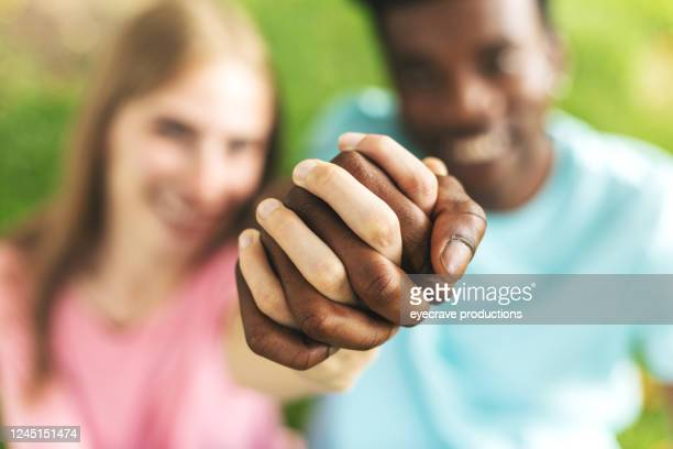 multi ethnic heterosexual generation z couple holding hands - preconceito racial imagens e fotografias de stock