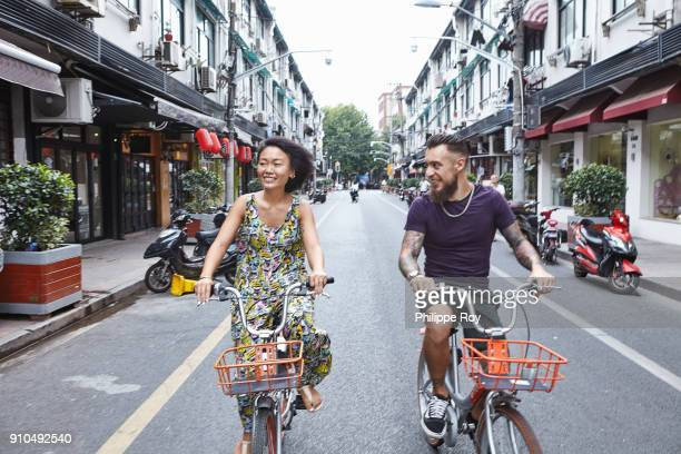 multi ethnic hipster couple cycling along city street, shanghai french concession, shanghai, china - french quarter stock photos and pictures