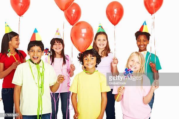 Multi ethnique enfants tenant rouge ballons d'une fête d'anniversaire