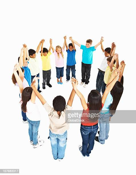 multi ethnic kids playing in circle with hands raised - children only stock pictures, royalty-free photos & images