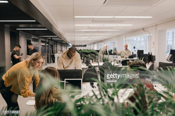 multi ethnic professionals discussing while working at desk in open office space - employee engagement stock pictures, royalty-free photos & images