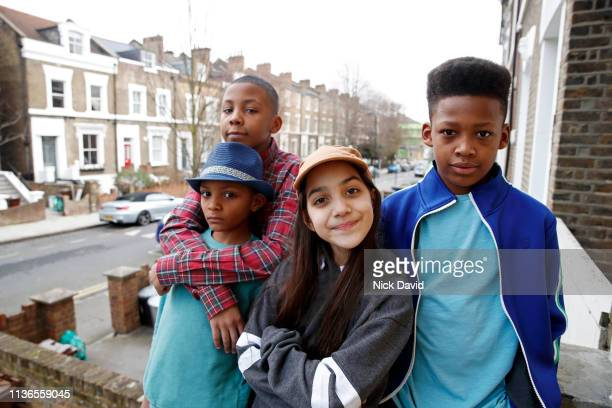 Multi ethnic siblings looking at camera outside townhouse