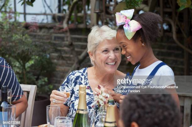 Multi ethnic smiling grandmother and granddaughter enjoying lunch on patio