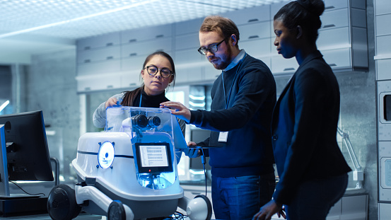 Multi Ethnic Team of Male and Female Leading Scientists Work on Innovative Robotics Technology. They Work in a Modern Laboratory/ Research Center. 1167549720