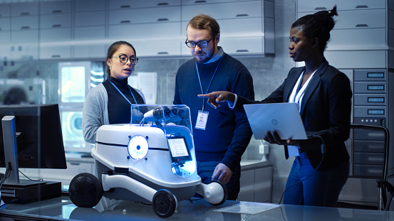 Multi Ethnic Team of Male and Female Leading Scientists Work on Innovative Robotics Technology. They Work in a Modern Laboratory/ Research Center. 1167549773