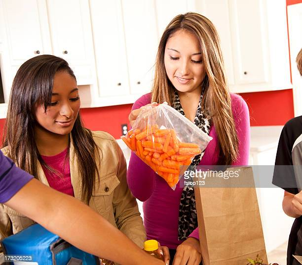 Multi ethnic teens in kitchen making school lunches