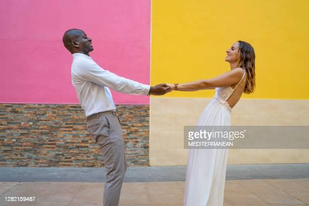 multi etniska turistpar i kärlek i färgglada rosa och gula fasader som håller händerna - flerfärgad klänning bildbanksfoton och bilder