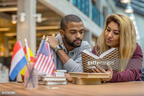 Multi ethnic university adult student couple learning languages together in a study hall