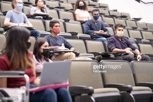 multi ethnic university students in lecture hall - fatcamera stock pictures, royalty-free photos & images