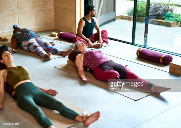 multi ethnic yoga group relaxing at end of session - participant stock pictures, royalty-free photos & images