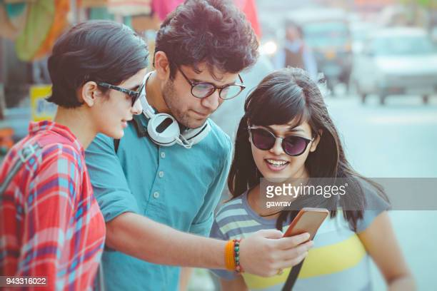 Multi ethnic young adult friends sharing smartphone together.