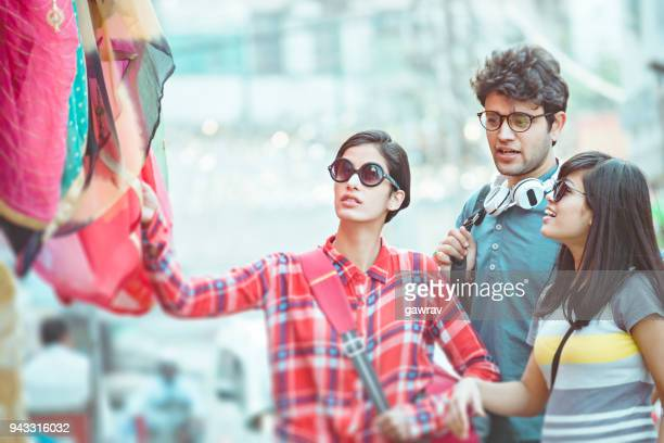 Multi ethnic young adult friends shopping together in city.
