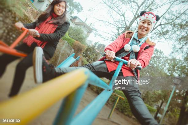 Multi ethnic young female friends playing seesaw in park.
