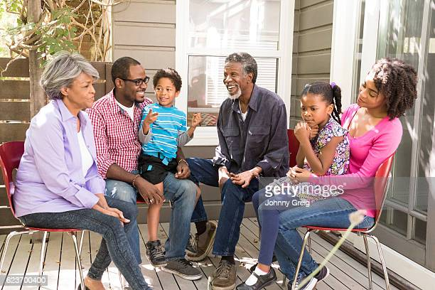 Multi generation African American family on decking outside house