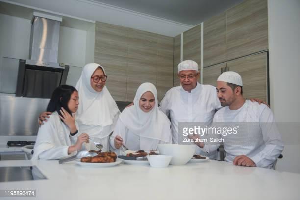 multi generation asian muslim family gathered for hari raya puasa - hari raya celebration stock pictures, royalty-free photos & images