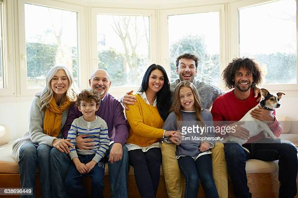 Multi generation family and dog on window seat looking at camera smiling