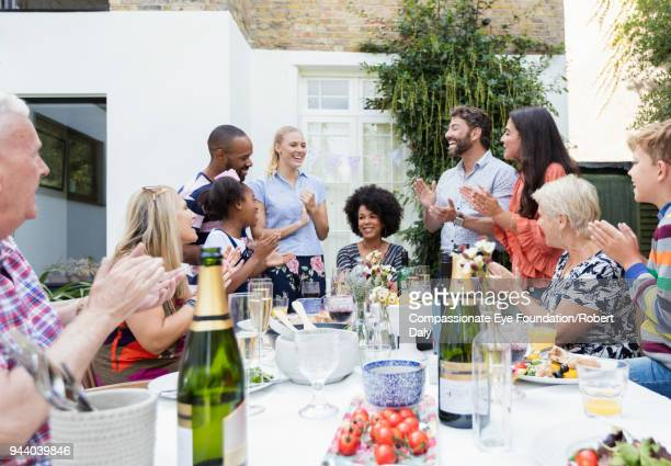 multi generation family clapping celebrating lunch at patio table - garden party stock pictures, royalty-free photos & images