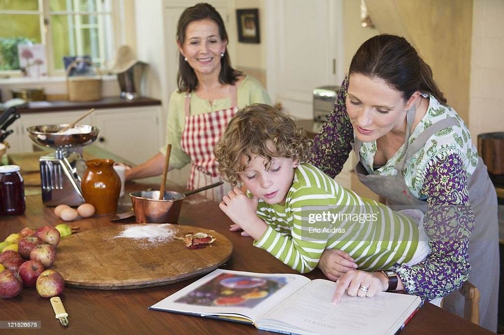 Multi generation family cooking food at kitchen : Stock Photo