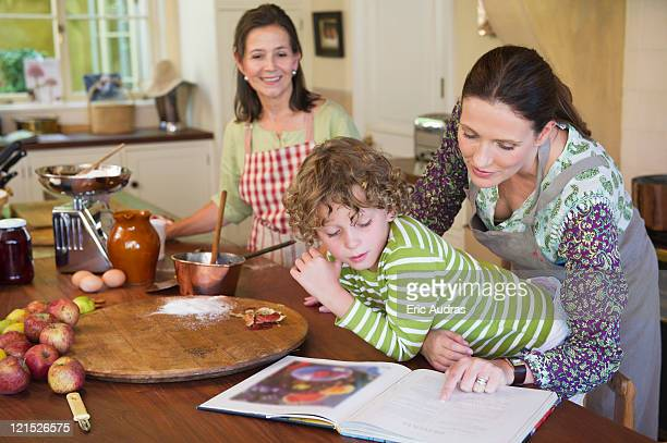 multi generation family cooking food at kitchen - 40 44 jaar stock pictures, royalty-free photos & images