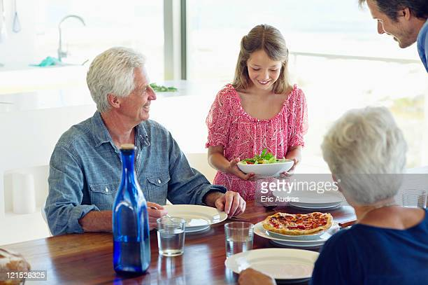 Multi generation family eating food at a dining table