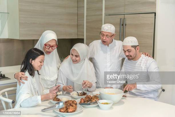 multi generation family eating in a kitchen - hari raya celebration stock pictures, royalty-free photos & images