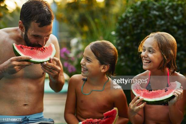 multi generation family enjoy watermelon near backyard pool - cochlear implant stock pictures, royalty-free photos & images