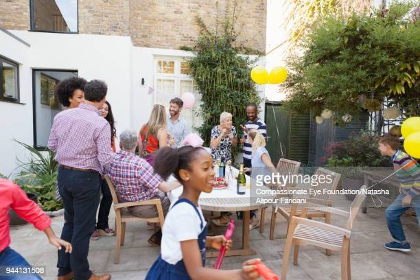 multi generation family enjoying birthday celebration lunch at garden patio table - social gathering stock pictures, royalty-free photos & images