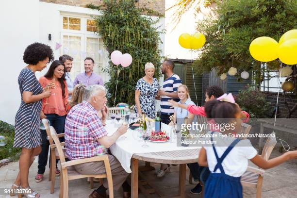 multi generation family enjoying birthday celebration lunch at garden patio table - birthday balloons stock photos and pictures